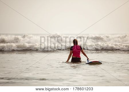Surfer girl trying to catch a wave on the sea