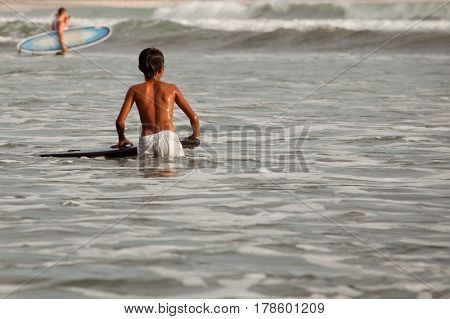 Boy surfer trying to catch a wave on the sea