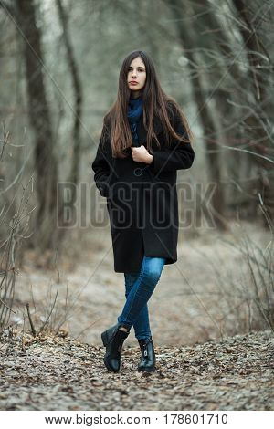 Young Beautiful Girl In A Black Coat Blue Scarf Exproring Autumn / Spring Forest Park. An Elegant Br