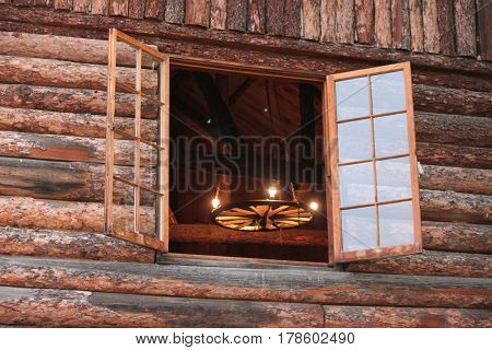 Country Chandelier through an Open Log Cabin Window