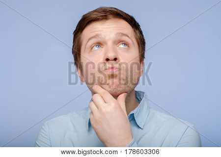 Young Man Thinking About Something Difficult, Compressing His Lips And Rubbing His Chin