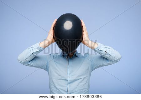 A White Man Covers His Face With A Black Balloon. Hiding From Problems