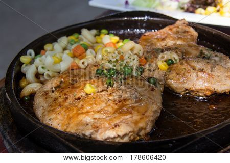 Close up of delicious grilled seafood platter. grilling steaks on flaming grill and shot with selective focus. rare steak black rectangular plate tomatoes on a black wooden background.