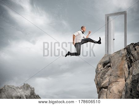 Businessman jumping over the mountains to reach a door. concept of ambition in business