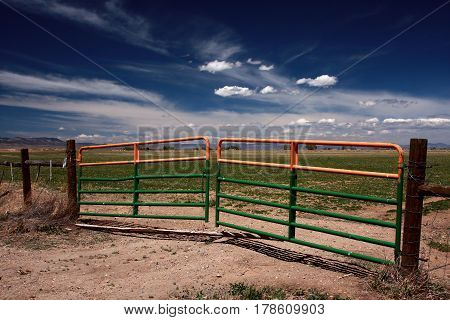Metal gates provide access to an irrigated farming field beneath crisp blue spring skies near Alamosa, Colorado