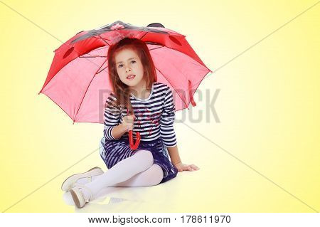 Beautiful little girl long hair and white bow on her head , in a summer dress in stripes.She's sitting on the floor hiding under the umbrella.On a yellow gradient background.