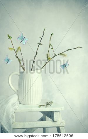Spring still life with sprigs of catkin plant in ceramic jug and styiised butterflies
