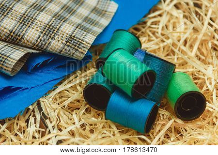 Cotton thread bobbins and cloth on wooden shavings, sewing material