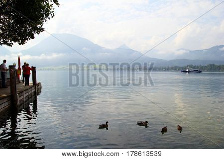 Travel To Sankt-wolfgang, Austria. The Ducks On The Lake Wolfgangsee Near To Mountains In The Cloudy