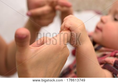 Gentle stroking the mother of the hands of her one-year-old child.