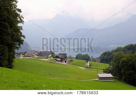 Travel To Sankt-wolfgang, Austria. The View On The Green Meadow With The Houses, A Lake And The Moun