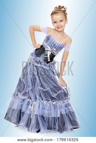 Slender little girl , with beautiful hair on his head, elegant long Princess dress.The girl twisted to the side and keeps his hand on his knee.On the pale blue background.