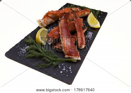 Boiled crab legs with lemon slices and dill on black plate on white background
