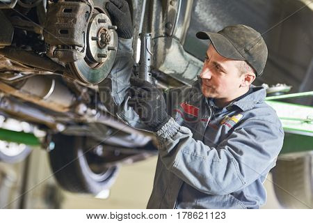 Auto repair service. Mechanic inspecting car suspension