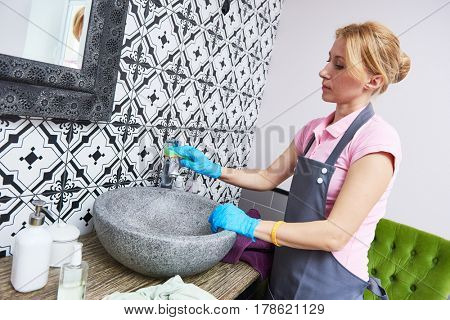 Cleaning service. woman clean washbowl at bathroom