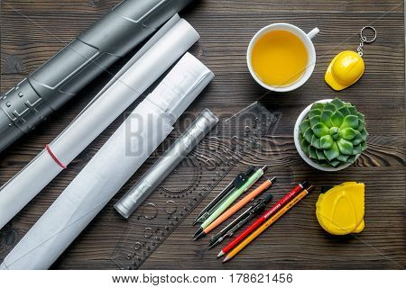 architect working desk with cup of tea, project and pens on wooden background top view