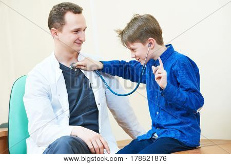 child boy examining male doctor with stethoscope in hospital