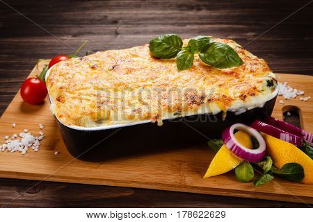Lasagna served on cutting board