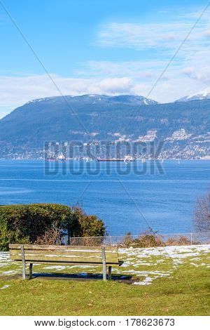 View on Vancouver Downtown and Mountains over ocean and a park bench on the foreground. British Columbia. Canada.