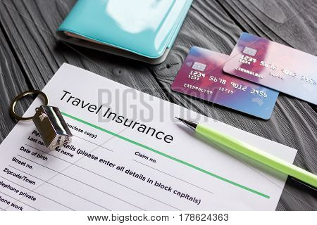 Travel insurance application form with credit cards and passport on gray wooden desk background