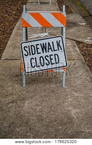 Sidewalk Closed Sign Askew with Copy Space Below over sidewalk