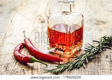 extra oil in carafe with spices and fresh chili on wooden desk background mock-up