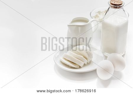 monochrome concept with dairy products for proteic breakfast on white table background mock up