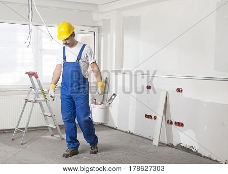 Construction Worker with Mustache Carrying Work Tools