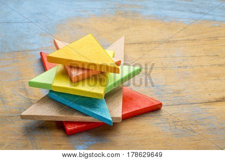 stack of seven colorful tangram wooden pieces, a traditional Chinese puzzle game on a grunge wooden background