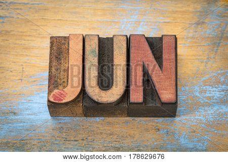 June month in vintage letterpress wood type against grunge wooden background