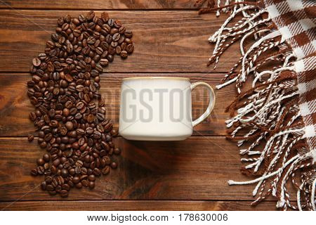 Cup, coffee beans and plaid on wooden background