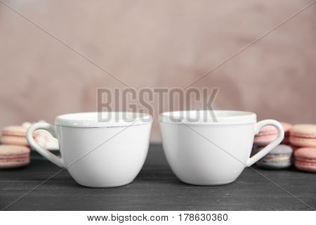 White cups and cookies on grey table