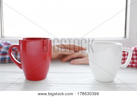Cups and hands near window