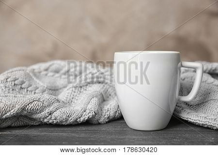 White cup and knitted scarf on grey table