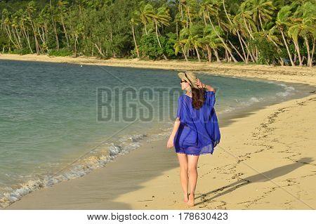 Tourist Woman Walks Along A Tropical Beach In Fiji