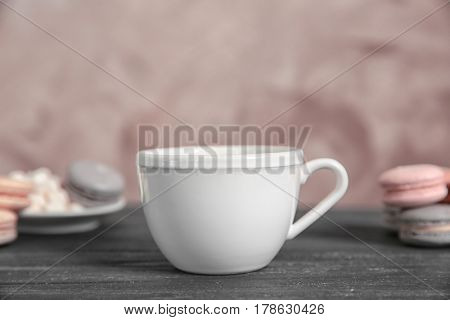 White cup and cookies on grey table