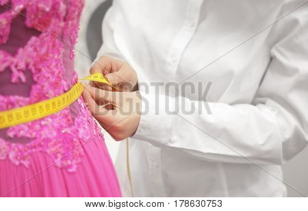 Woman checking measurement of evening dress at fashion atelier