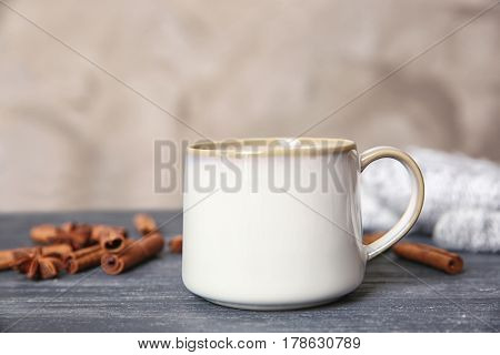 White cup and cinnamon sticks on grey table