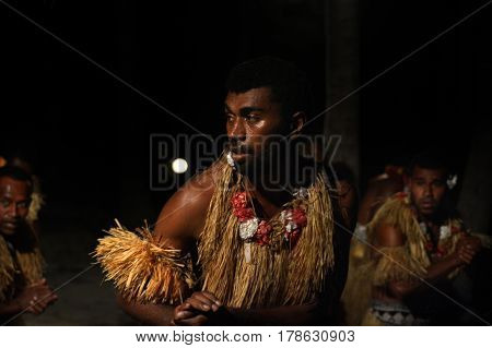 Indigenous Fijian men dancing a traditional male dance meke wesi the spear dance. Real people copy space