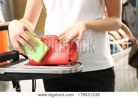 Laundry worker washing little bag at dry-cleaning