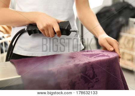 Laundry worker removing stains using special equipment