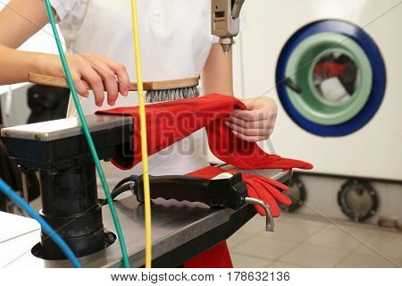 Laundry worker cleaning gloves with brush at dry-cleaning