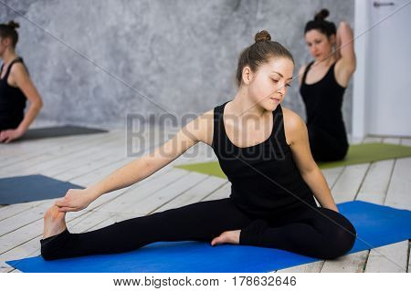 Shot of young women warming up before yoga session. Young people sitting on exercise mat in yoga class