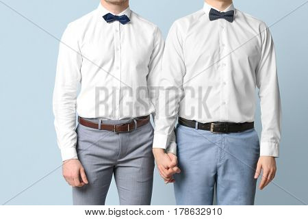 Happy gay couple holding hands together on color background
