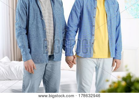 Happy gay couple holding hands together at home