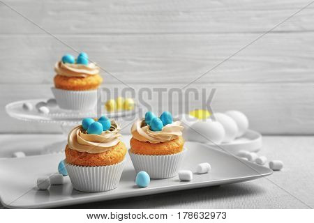 Easter cupcakes on table against grey wooden background