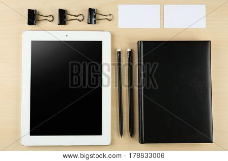 Notebook, tablet and business cards on wooden background