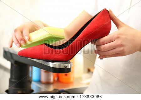Laundry worker cleaning high heels with sponge at dry-cleaning, closeup