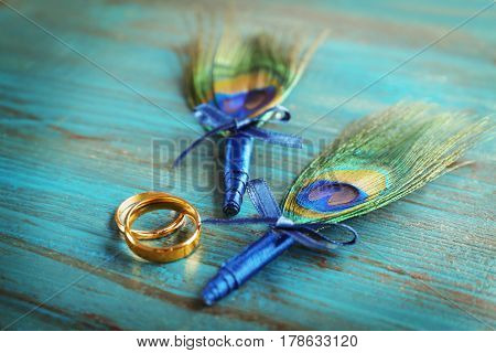 Wedding rings and boutonnieres with peacock feather on wooden background