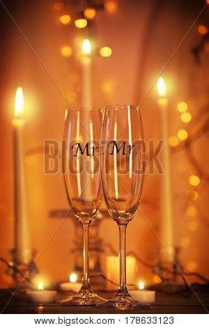 Decorated champagne glasses for gay wedding on table